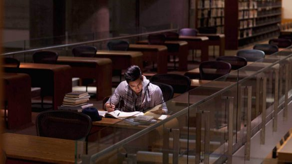 Student studying in library alone