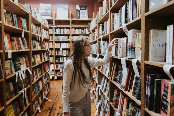 Girl grabbing book off bookshelf